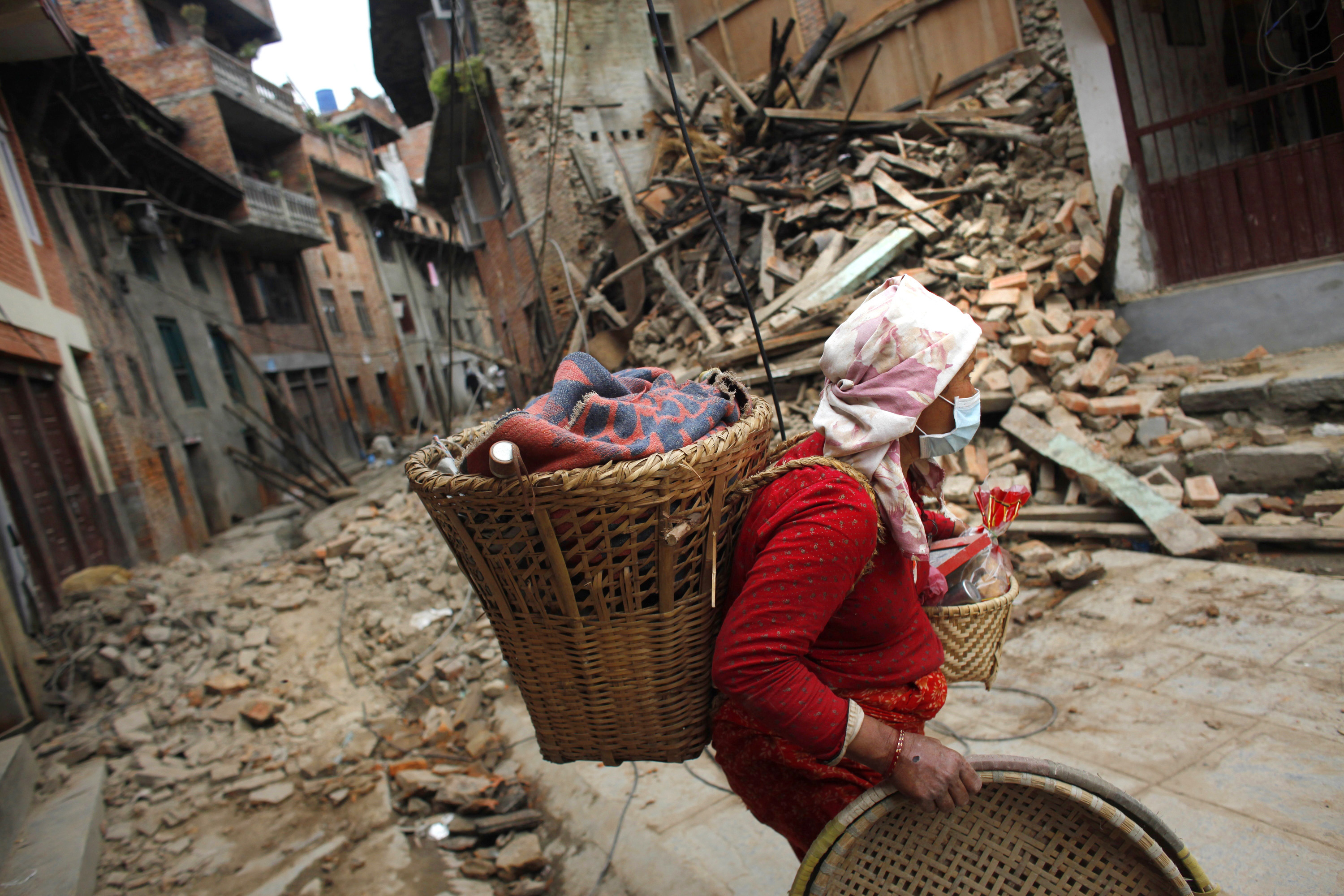 FILE - In this Thursday, April 30, 2015, file photo, a Nepalese woman salvages her belongings from her damaged house in earthquake in Khokana, Nepal.  The violence of the 7.8-magnitude earthquake left countless towns and villages across central Nepal in a shambles. Almost one year later, a shambles they remain. (AP Photo/Niranjan Shrestha)
